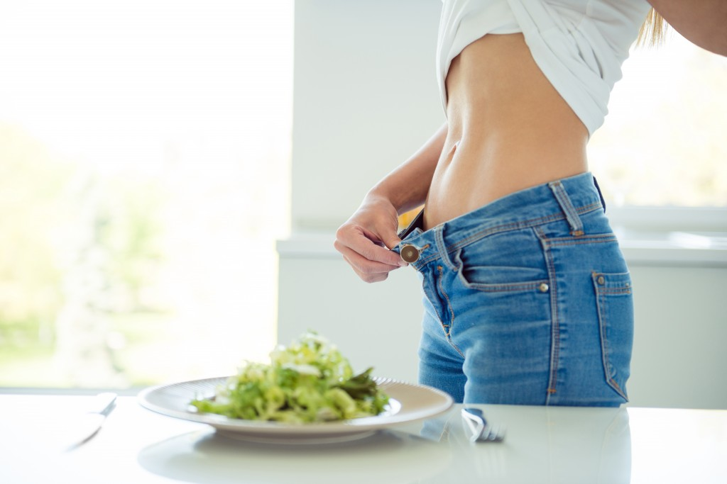 Vitamins life style small fresh green portion strength living concept. Side profile close up view photo of lady showing her perfect ideal abs pecs standing near table in white loft room